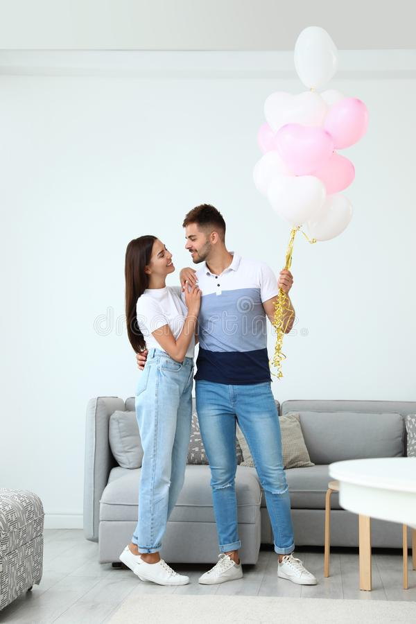 Young couple with air balloons at home.  of Saint Valentine`s Day stock photos