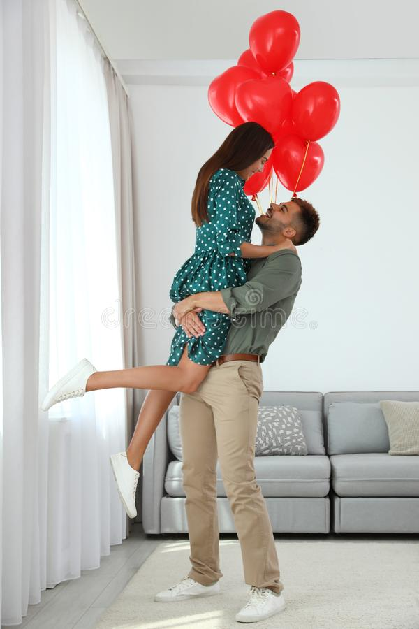 Young couple with air balloons at home.  of Saint Valentine`s Day stock images