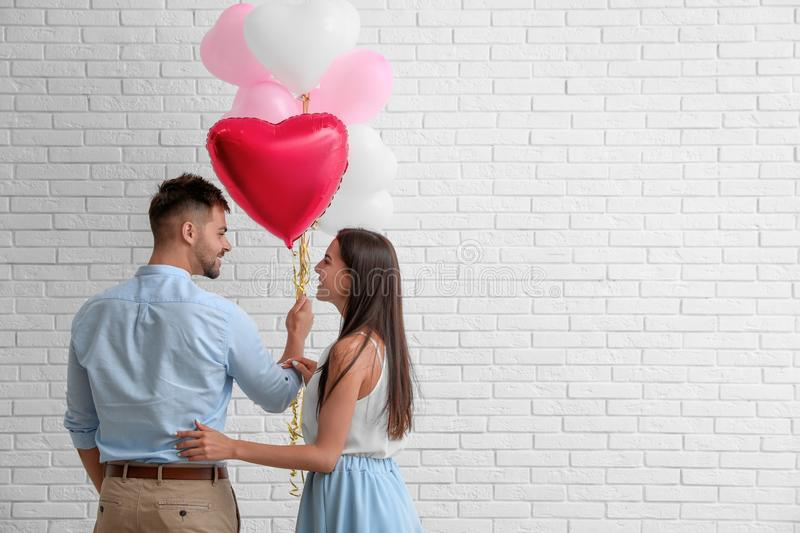 Young couple with air  near white brick wall. Celebration of Saint Valentine`s Day stock image