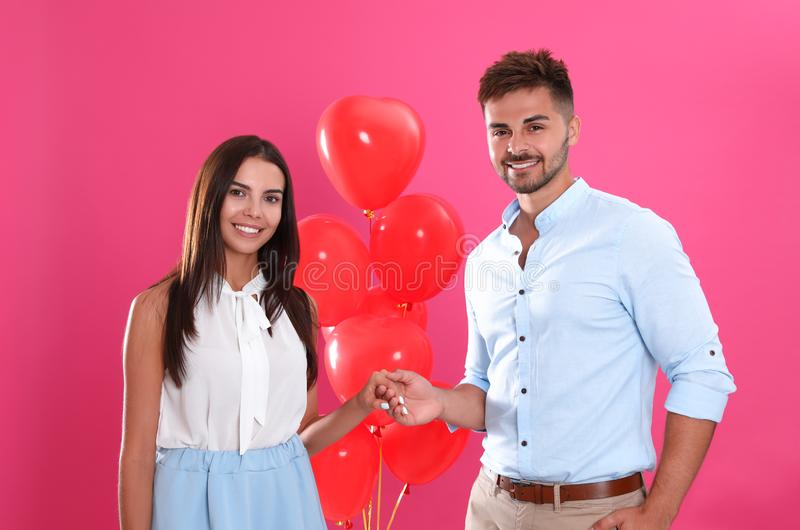 Young couple and air  on pink background. Celebration of Saint Valentine`s Day stock photos