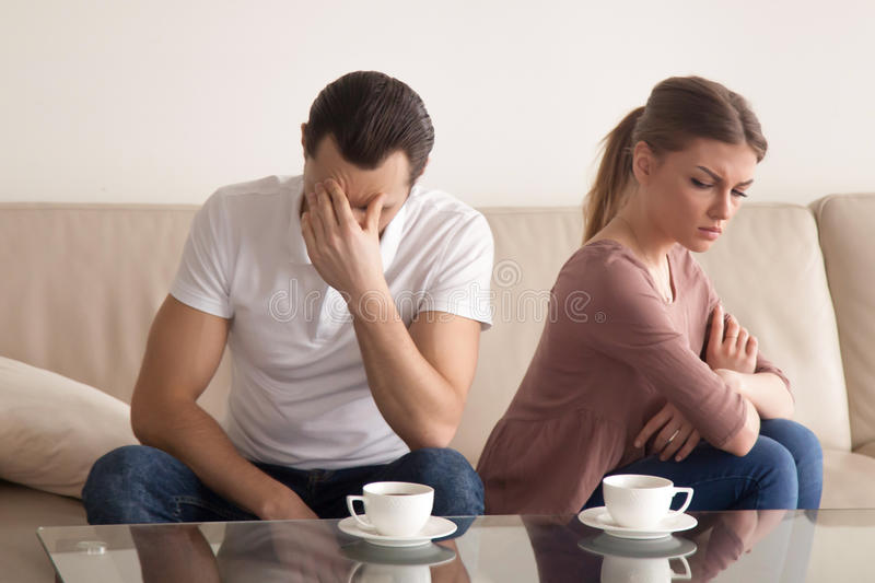 Young couple after arguing, guy tired of quarrelling, woman offe stock image
