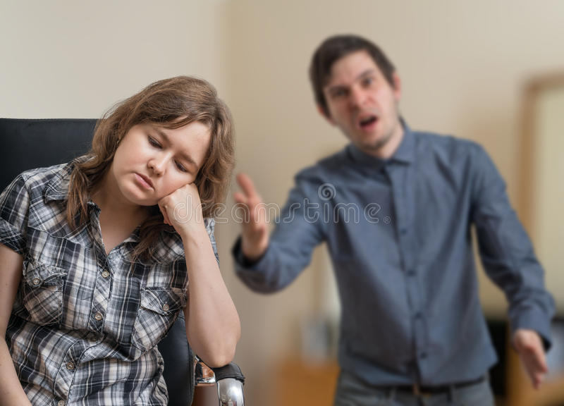 Young couple is arguing. Man is shouting and explaining something to sad woman. royalty free stock photography