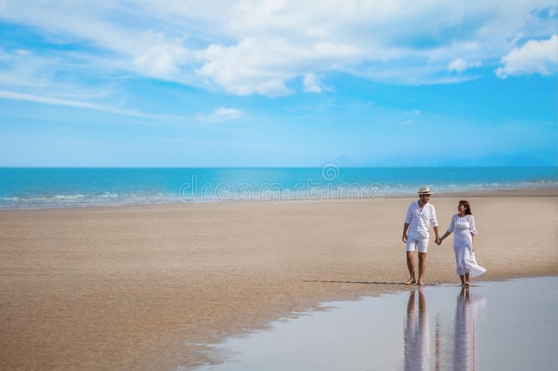 Young couple asian in love walking and holding hand together at sea beach on blue sky . happy smiling wedding with white dress royalty free stock photos