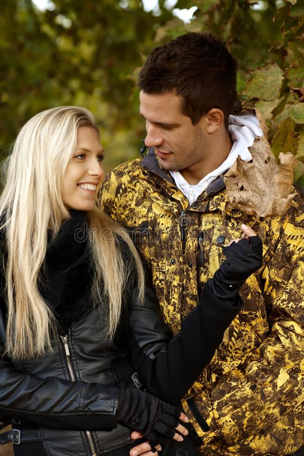Young Couple In Autumn Park Smiling Stock Photo