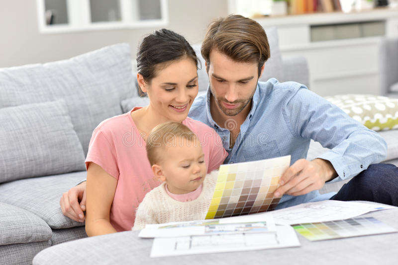 Young couple with baby choosing colour paint royalty free stock photo
