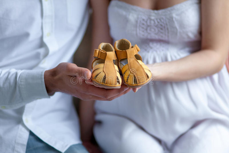 Young couple with baby shoes sitting at home. The young couple with baby shoes sitting on sofa at home stock images