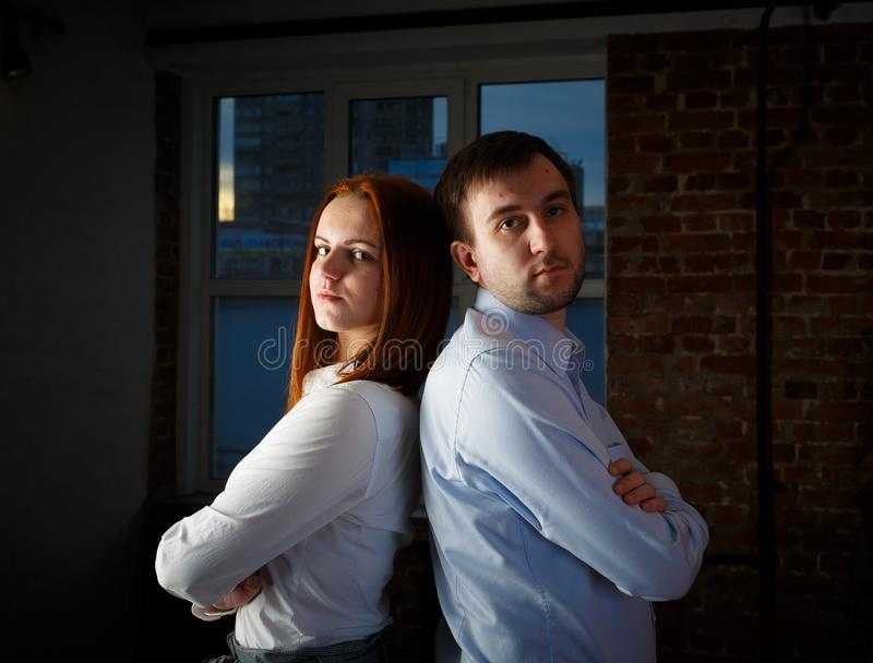 Young couple back to back looking at the camera in the background loft interior window. The concept of a new home for a young stock images