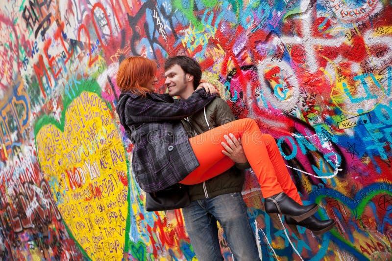 Young couple on the Background John Lennon Wall, Prague. Young couple in love on the Background John Lennon Wall. Prague, Czech Republic, Europe stock photo