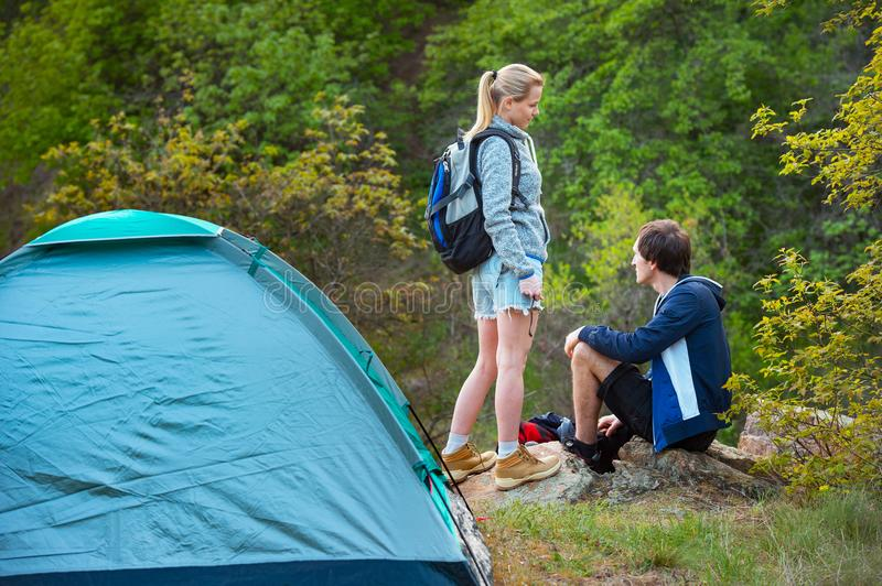 Young couple backpackers camping trip in forest at summer weekend. Travel, tourism, hike and people concept. royalty free stock photo