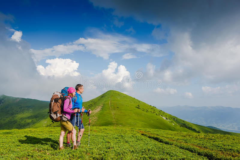 Young couple with backpacks hiking in the mountains stock images