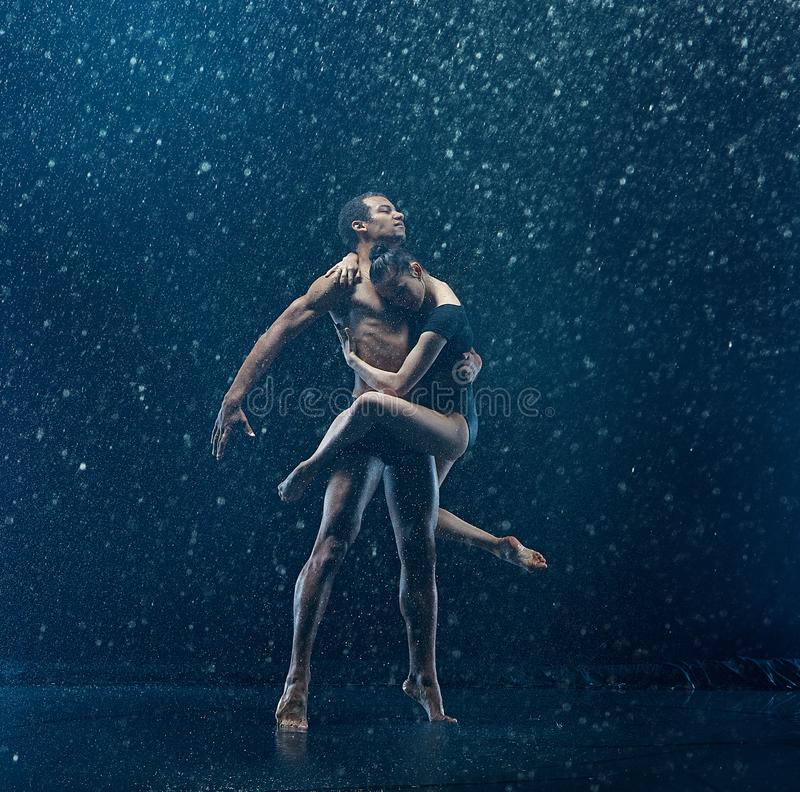 Young couple of ballet dancers dancing unde rwater drops royalty free stock photography