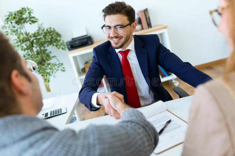 Young couple in bank office shaking hand to financial adviser. Portrait of young couple in bank office shaking hand to financial adviser royalty free stock image