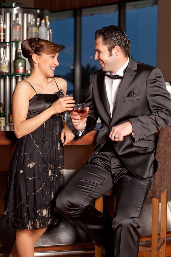 Young couple at bar drinking and flirting