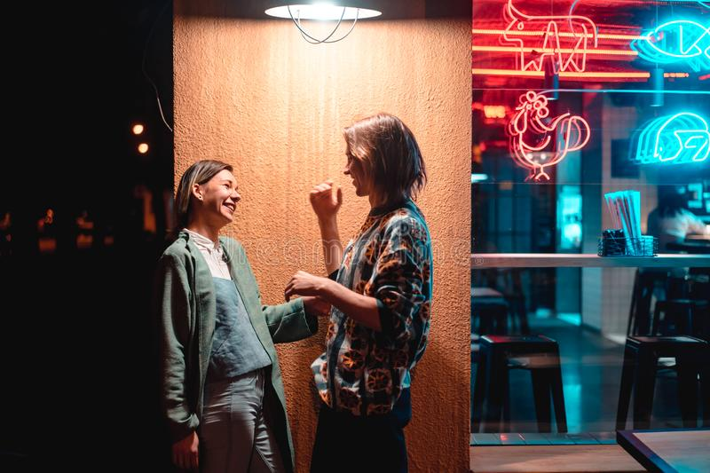 Young couple at the bar, street of the night city royalty free stock images