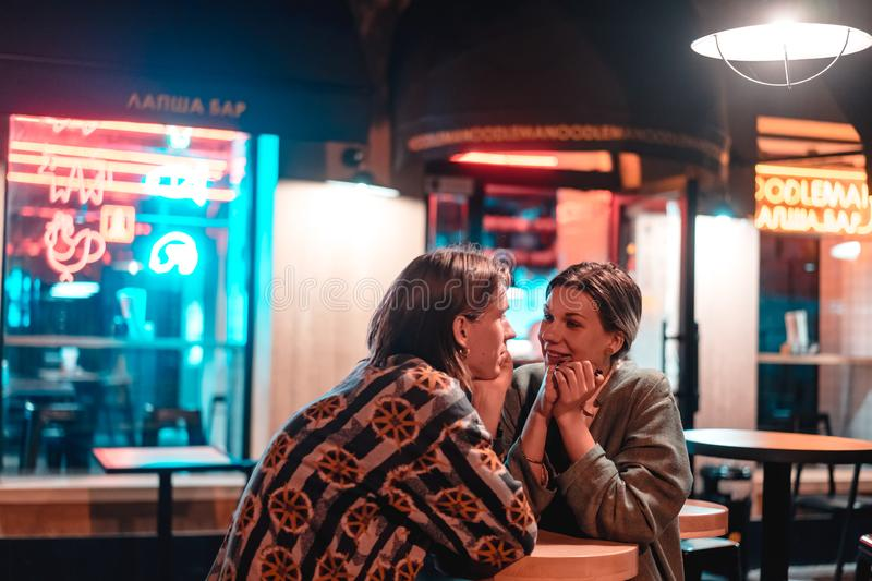 Young couple at the bar, street of the night city stock images