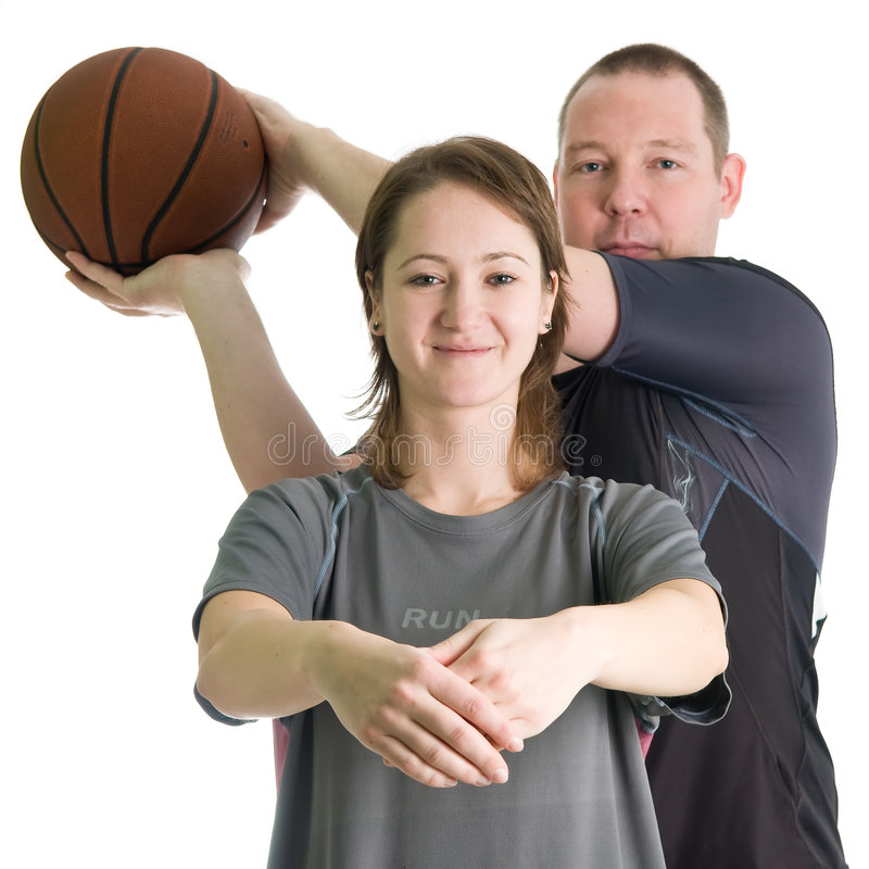Young couple with basketball ball. Girl in front creates basket, man from behind is about to score. Isolated over white royalty free stock photos