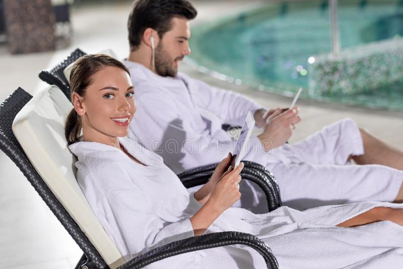 young couple in bathrobes using digital devices while resting near pool royalty free stock images