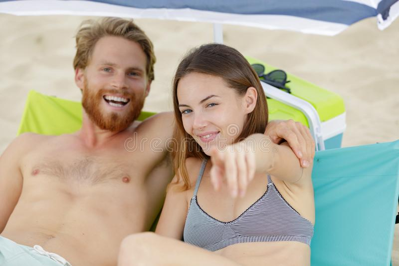 Young couple on beach pointing forwards. Young couple on the beach pointing forwards stock photo