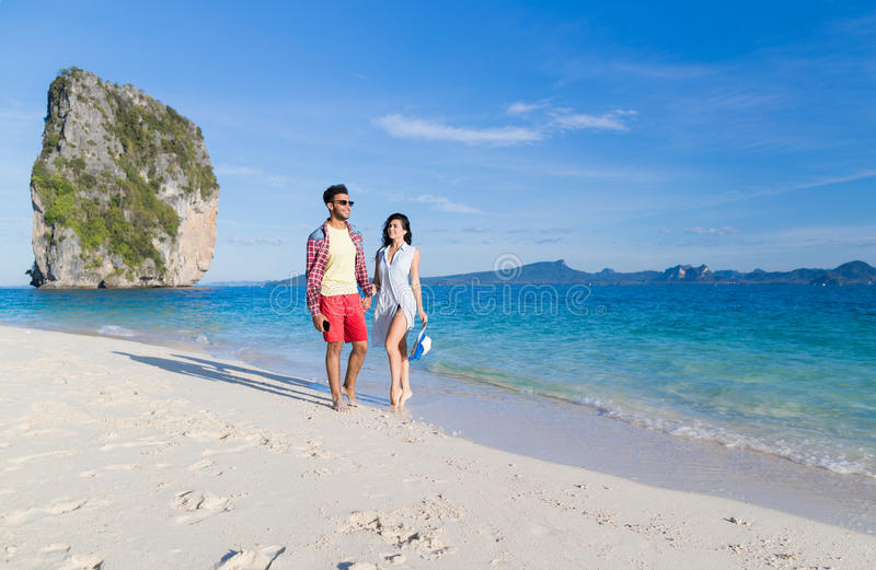 Young Couple On Beach Summer Vacation, Happy Smiling Man And Woman Walking Seaside. Sea Ocean Holiday Travel royalty free stock photo