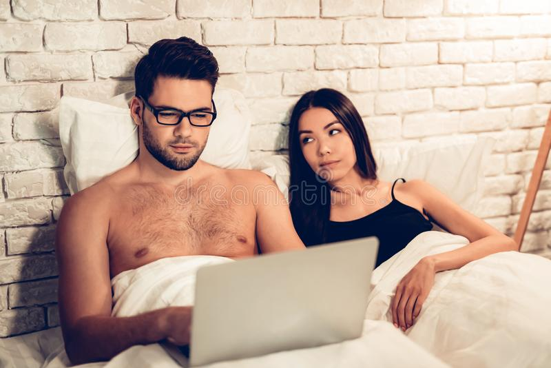 Young Couple in Bed, Man Working Laptop Bored Wife royalty free stock image