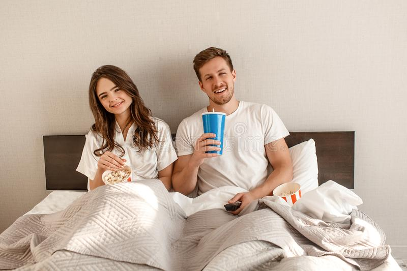 Young couple in the bed. Smiling beautiful man and woman are eating popcorn and watching TV together in bedroom stock image