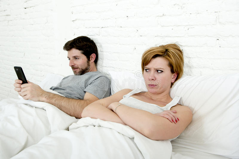 Young couple in bed unsatisfied wife bored frustrated and angry while internet addict husband is using mobile phone social networ. Young couple in bed stock image
