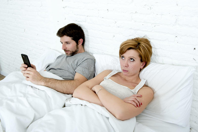 Young couple in bed unsatisfied wife bored frustrated and angry while internet addict husband is using mobile phone social networ. Young couple in bed stock photo