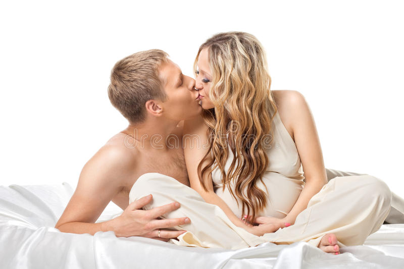 Young couple in bed wait for baby kiss together stock images