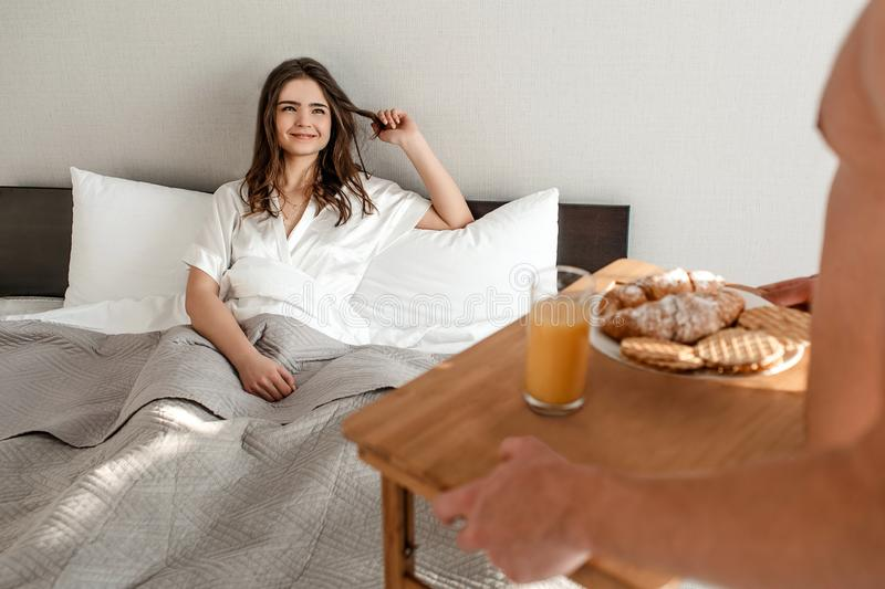 Young couple in the bed. Happy beautiful hungry woman is waiting for romantic breakfast in the morning royalty free stock photography