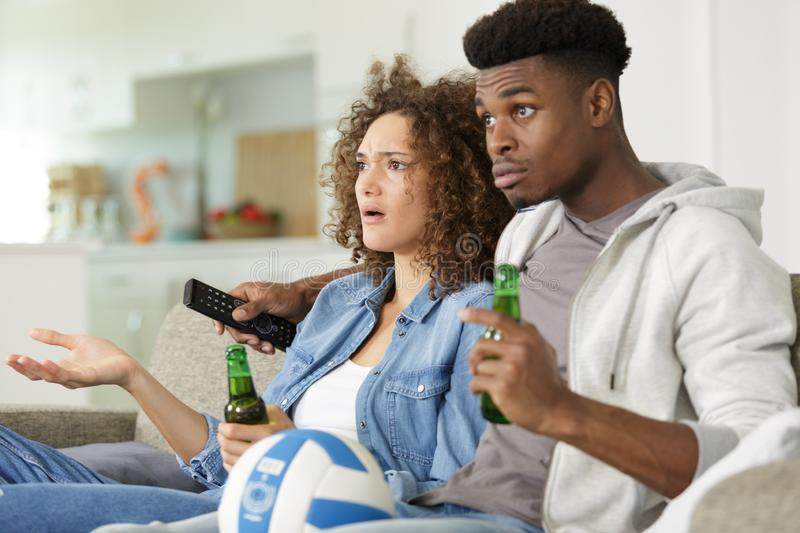 Young couple with beer watching tv at home royalty free stock photography