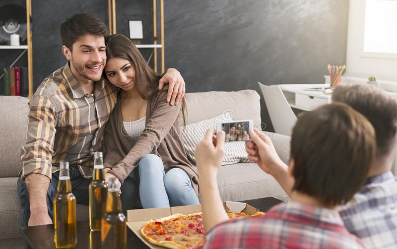 Young couple being photographed by friends at home party royalty free stock images