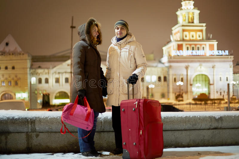 Young couple with big red trolley bag stands in evening royalty free stock photo