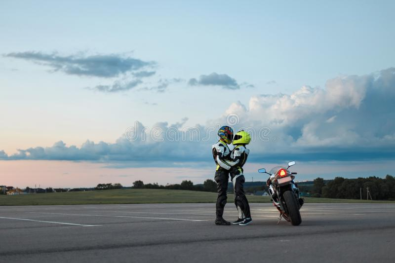 Young couple in biker suits near a motorcycle. royalty free stock photos