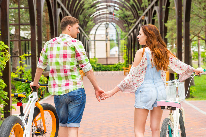 Young couple with bikes holding hands in archway royalty free stock images