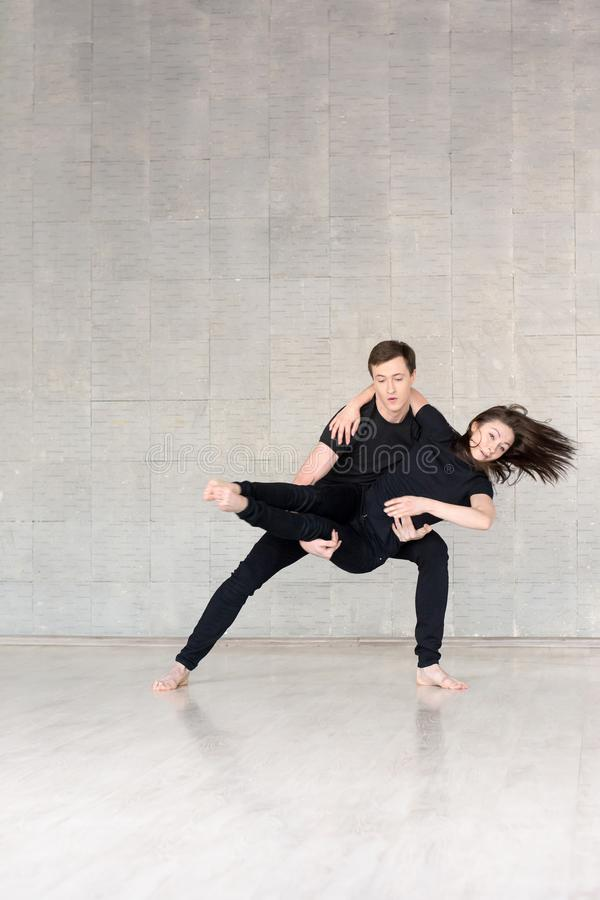 Young couple in black dancing. royalty free stock image