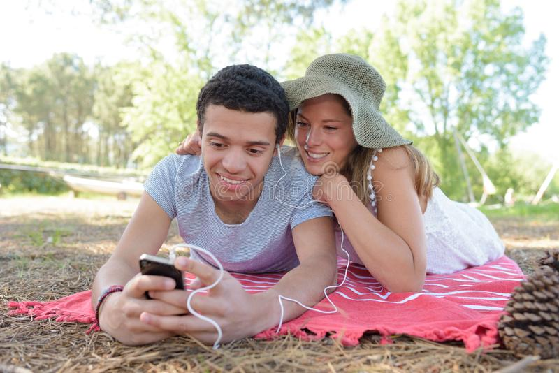 Young couple on blanket outdoors sharing earphones royalty free stock images