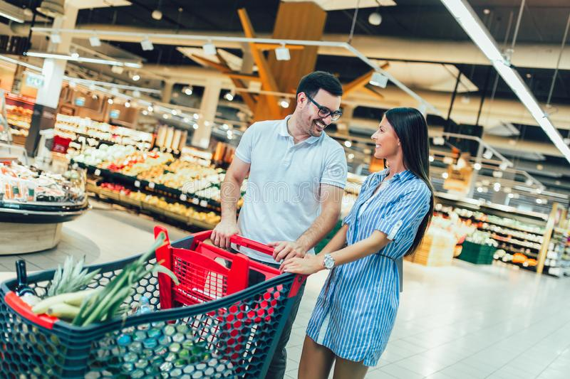 Young couple bonding to each other and smiling while walking while walking in food store with shopping cart royalty free stock image