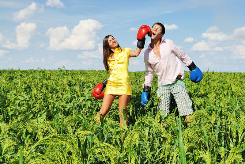 Young couple boxing. On green field royalty free stock photo