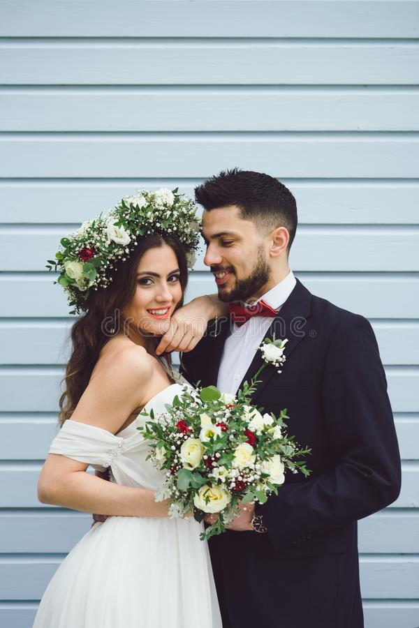 Bride groom flowers smile wedding posing. Young couple bride groom getting married wedding posed photos at seaside sea beach hairpiece flowers bouquet church royalty free stock photos
