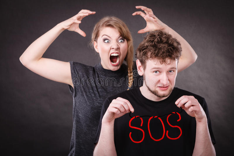Young couple with broken heart and sos word. Betrayal and break up in relationship. Young couple arguing and holding red sos word sign symbol. Blonde women in royalty free stock photography