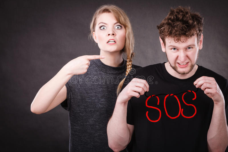 Young couple with broken heart and sos word. Betrayal and break up in relationship. Young couple arguing and holding red sos word sign symbol. Blonde women in royalty free stock photo