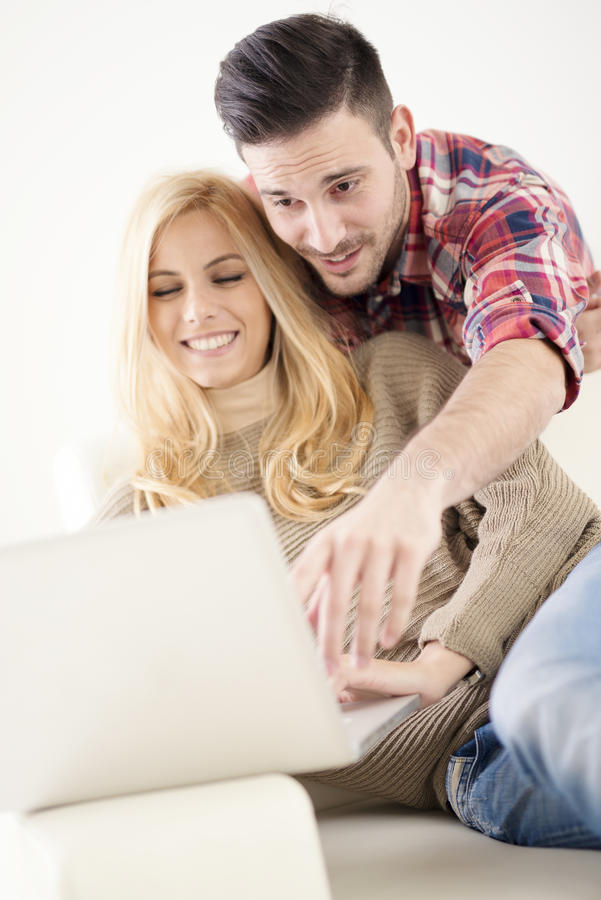 Young couple browsing internet at home,using laptop and smiling royalty free stock photo