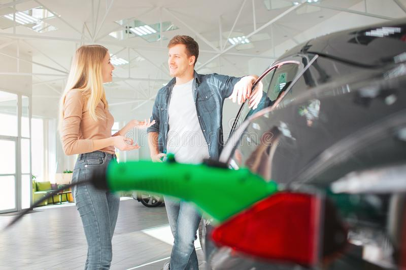 Young couple buying a first electric car in a showroom. Ecological vehicle concept. Modern technology in the automotive royalty free stock photography