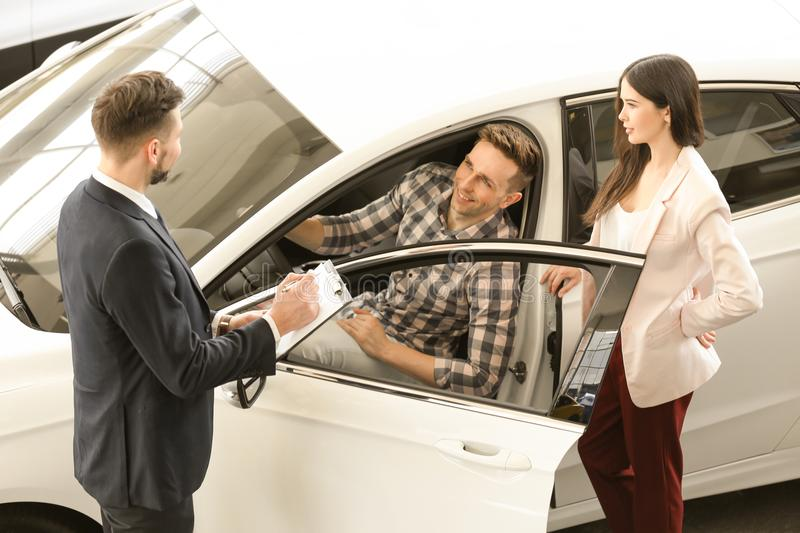 Young couple buying new car. In salon stock photos