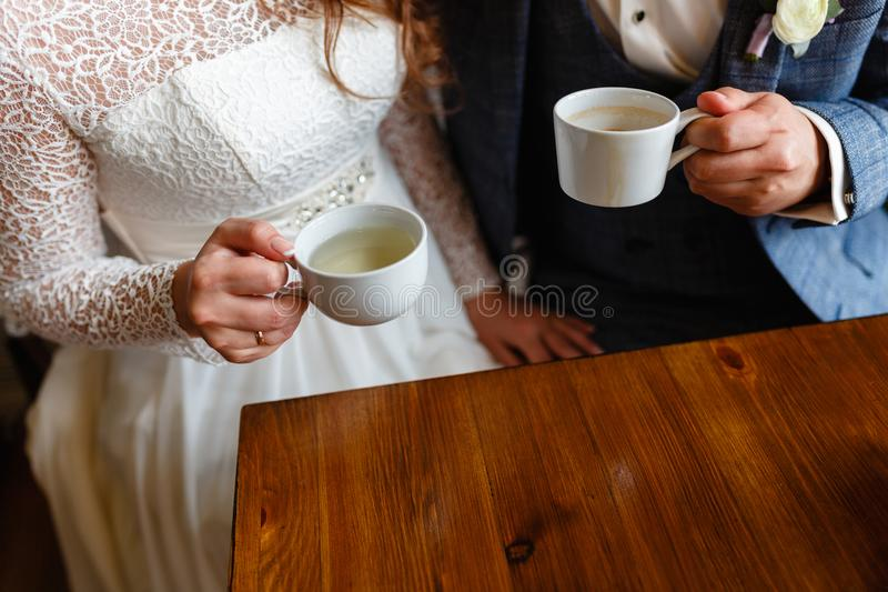 Young couple in a cafe in the attic drinking coffee and tea, sitting. Morning breakfast at the hotel. Cropped image of couple in l stock photos