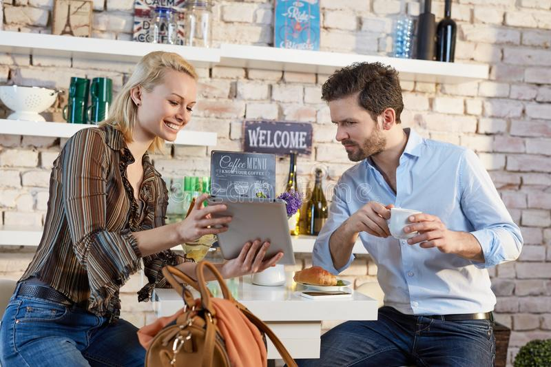 Young couple in cafeteria. Using tablet, smiling stock photos