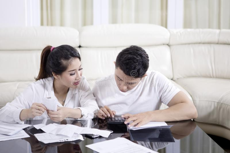 Young couple calculating their household finance. Picture of a young women calculating their household finance with her husband. Shot at home royalty free stock photos