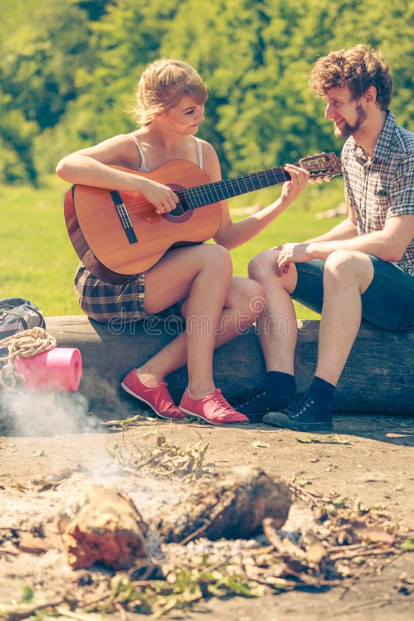 Young couple camping playing guitar outdoor stock photography