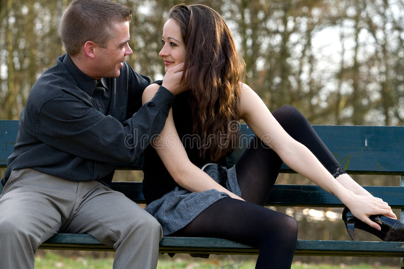Young couple caring. Man and girlfriend on a park bench caring stock image