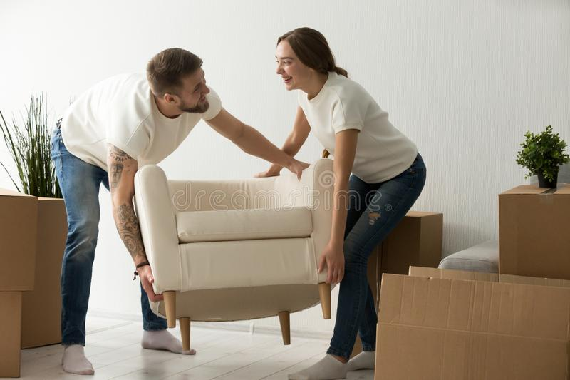 Young couple carrying chair together, placing furniture in new h stock image